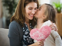 Caucasian girl giving Valentine to mother