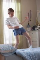 Caucasian boy standing on bed playing air guitar 11018039811| 写真素材・ストックフォト・画像・イラスト素材|アマナイメージズ
