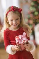 Smiling girl holding Christmas gift 11018040832| 写真素材・ストックフォト・画像・イラスト素材|アマナイメージズ