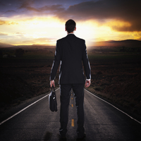 Caucasian businessman standing on remote highway at sunset