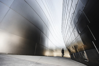 Businessman walking in urban alley
