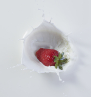 Strawberry dropping into milk