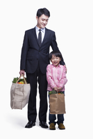 Chinese businessman and son carrying groceries