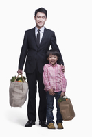 Chinese businessman and son carrying groceries 11018042782| 写真素材・ストックフォト・画像・イラスト素材|アマナイメージズ