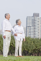Older Chinese couple standing in urban park