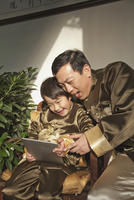 Chinese father and son using digital tablet 11018042907| 写真素材・ストックフォト・画像・イラスト素材|アマナイメージズ