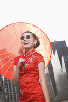 Glamorous Chinese woman in traditional clothing with parasol