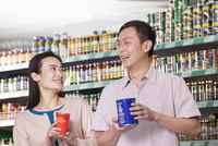 Chinese couple holding cans in grocery store