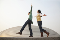 Chinese couple balancing on wall