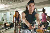 Chinese man riding stationary bicycle in gym 11018043011| 写真素材・ストックフォト・画像・イラスト素材|アマナイメージズ