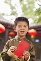 Chinese boy in traditional clothes holding red envelope