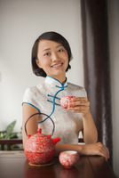 Chinese woman in traditional clothes having tea