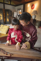 Chinese father and son in traditional clothes playing harp