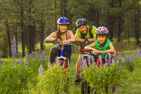 Family sitting on bicycles in meadow