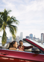 African American couple driving in convertible
