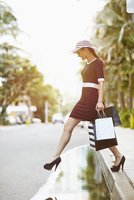 Pacific Islander woman with shopping bags on city street