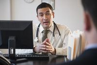 Doctor talking to clients in office 11018044250| 写真素材・ストックフォト・画像・イラスト素材|アマナイメージズ
