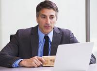 Hispanic businessman using tablet computer at desk