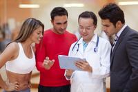 Hispanic people and doctor using tablet computer in gym 11018044747| 写真素材・ストックフォト・画像・イラスト素材|アマナイメージズ