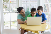 Hispanic father and sons using laptop