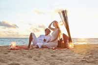 Caucasian couple relaxing on beach blanket