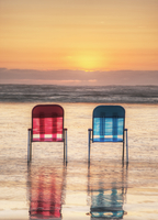 Lawn chairs in waves on beach at sunset