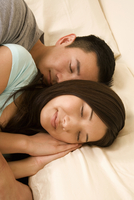 Chinese couple sleeping in bed