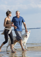 Caucasian couple jogging with dog on beach