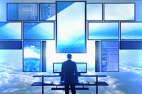 Caucasian businessman using multiple screens at desk in clouds 11018049281| 写真素材・ストックフォト・画像・イラスト素材|アマナイメージズ