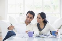 Indian couple paying bills in living room