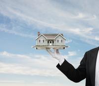 Caucasian butler holding house on platter
