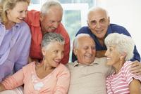 Senior friends talking in living room 11018049492| 写真素材・ストックフォト・画像・イラスト素材|アマナイメージズ