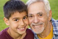 Older Hispanic man and grandson smiling