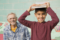 Older Hispanic man and grandson smiling outdoors