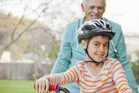 Older Hispanic man and grandson with bicycle