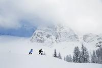 Caucasian hikers walking in snowy landscape 11018049581| 写真素材・ストックフォト・画像・イラスト素材|アマナイメージズ