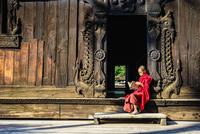 Asian monk reading by ornate doorway to temple 11018049591| 写真素材・ストックフォト・画像・イラスト素材|アマナイメージズ