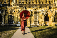 Asian man carrying umbrella by ornate temple