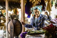 Asian woman spinning thread
