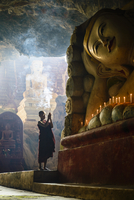Asian monk lighting incense in temple
