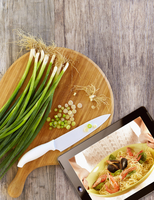 Digital tablet with picture of dish next to chopping board with fresh onions