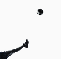 Leg of Black soccer player kicking ball