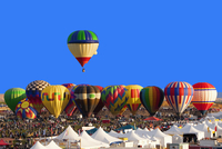 Hot air balloon floating above others at festival, Albuquerque, New Mexico, United States