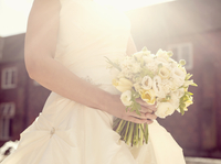 Close up of Hispanic bride holding bouquet of flowers