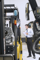 Hispanic businessman checking forklifts in warehouse