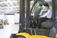 Hispanic businessman driving forklift in warehouse