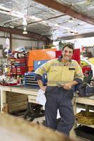 Hispanic mechanic smiling in workshop