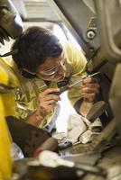 Hispanic mechanic working on machinery