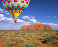 Hot air balloon flying over rock formation in desert landscape, Ayers Rock, Northern Territory, Australia