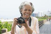 Older African American woman taking photographs on boardwalk